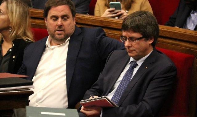 El president de la Generalitat, Carles Puigdemont, pren nota sota la mirada del vicepresident Oriol Junqueras