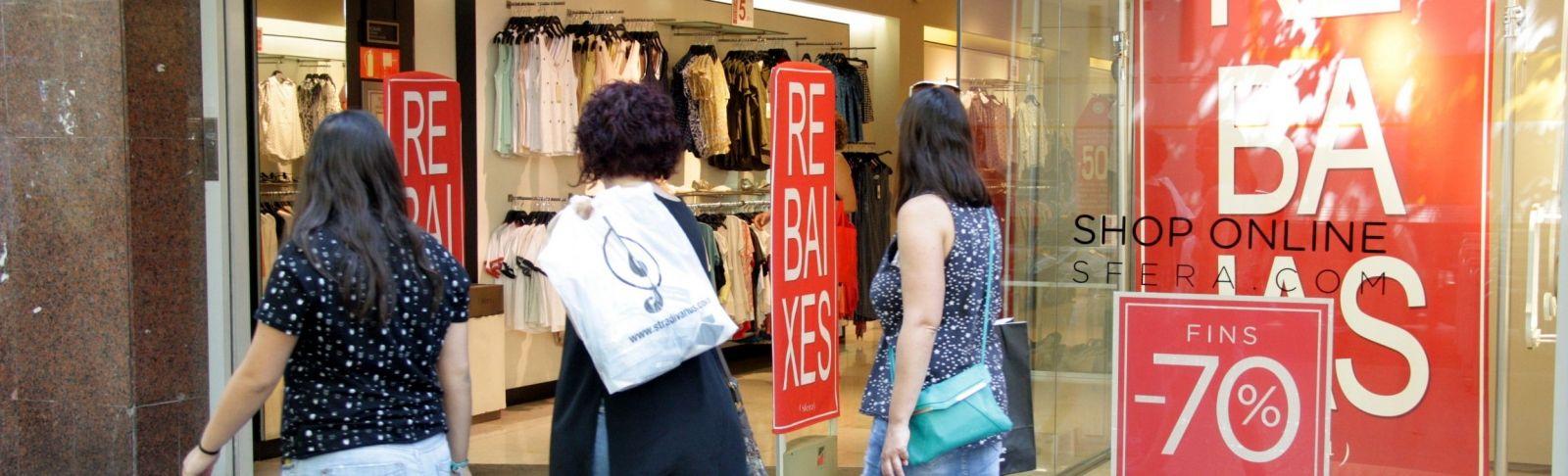 Tres dones amb bosses miren un aparador on hi ha els cartells que anuncien les rebaixes